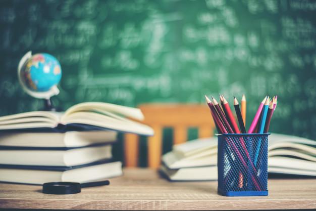Imagem de Livros, lousa e um conjunto de lápis, possui link para página de assuntos